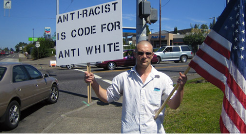 """Tyler Cole """"protesting the racist media"""" on the corner of SE McLoughlin Blvd and SE Concord Rd, Milwaukie, OR."""